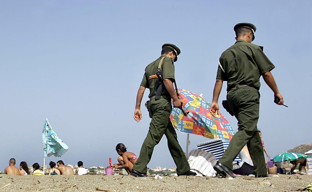 Algerian policemen patrol on a beach near Zeralda
