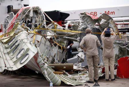 Airbus investigators examine part of the tail of AirAsia QZ8501 passenger plane in Kumai Port, near Pangkalan Bun, Central Kalimantan