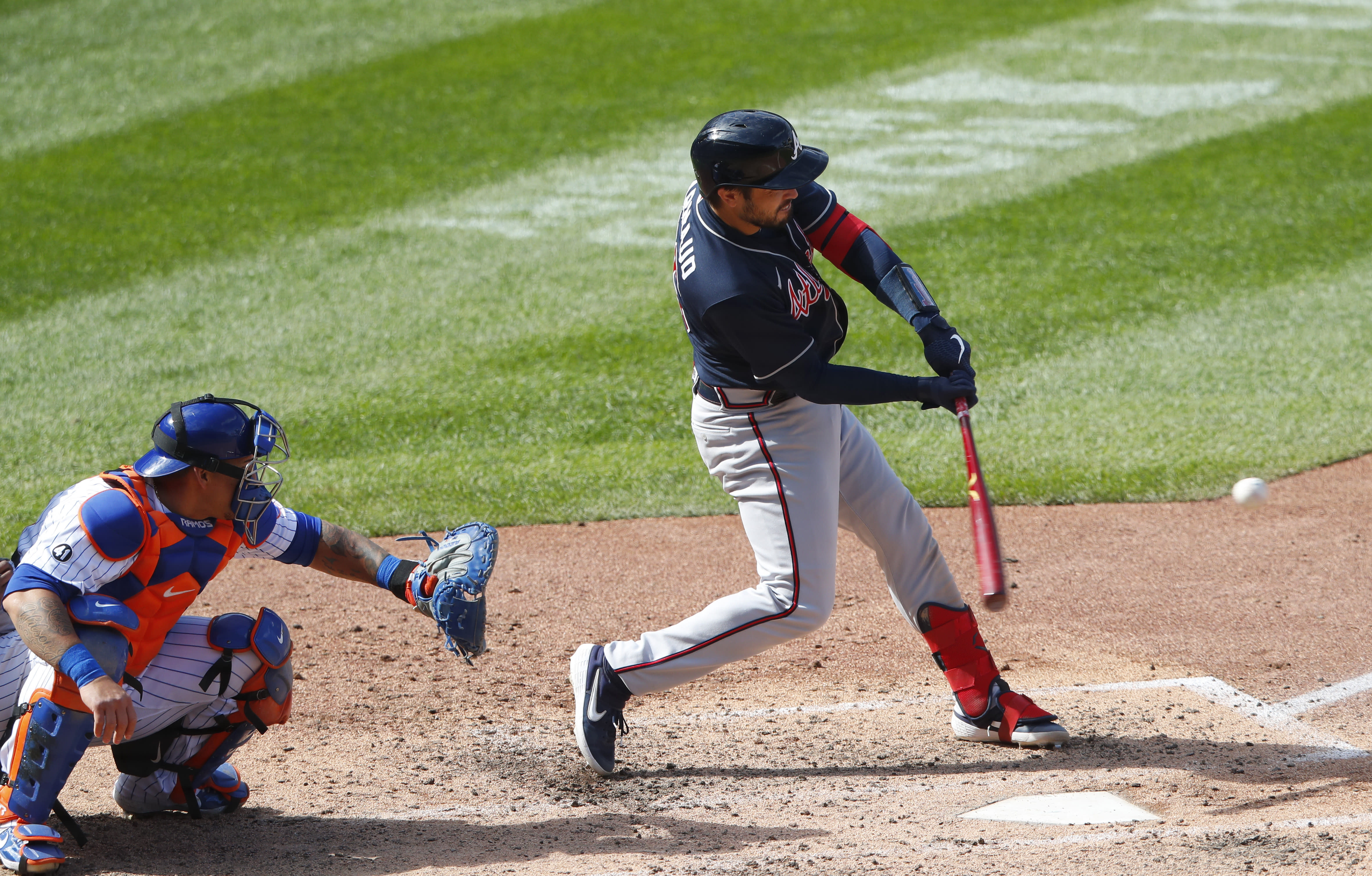 Atlanta Braves' Travis d'Arnaud, right, hits a double against the New York Mets during the sixth inning of a baseball game, Sunday, Sept. 20, 2020, in New York. (AP Photo/Noah K. Murray)