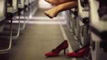 Plane passenger puts bare feet on woman's headrest