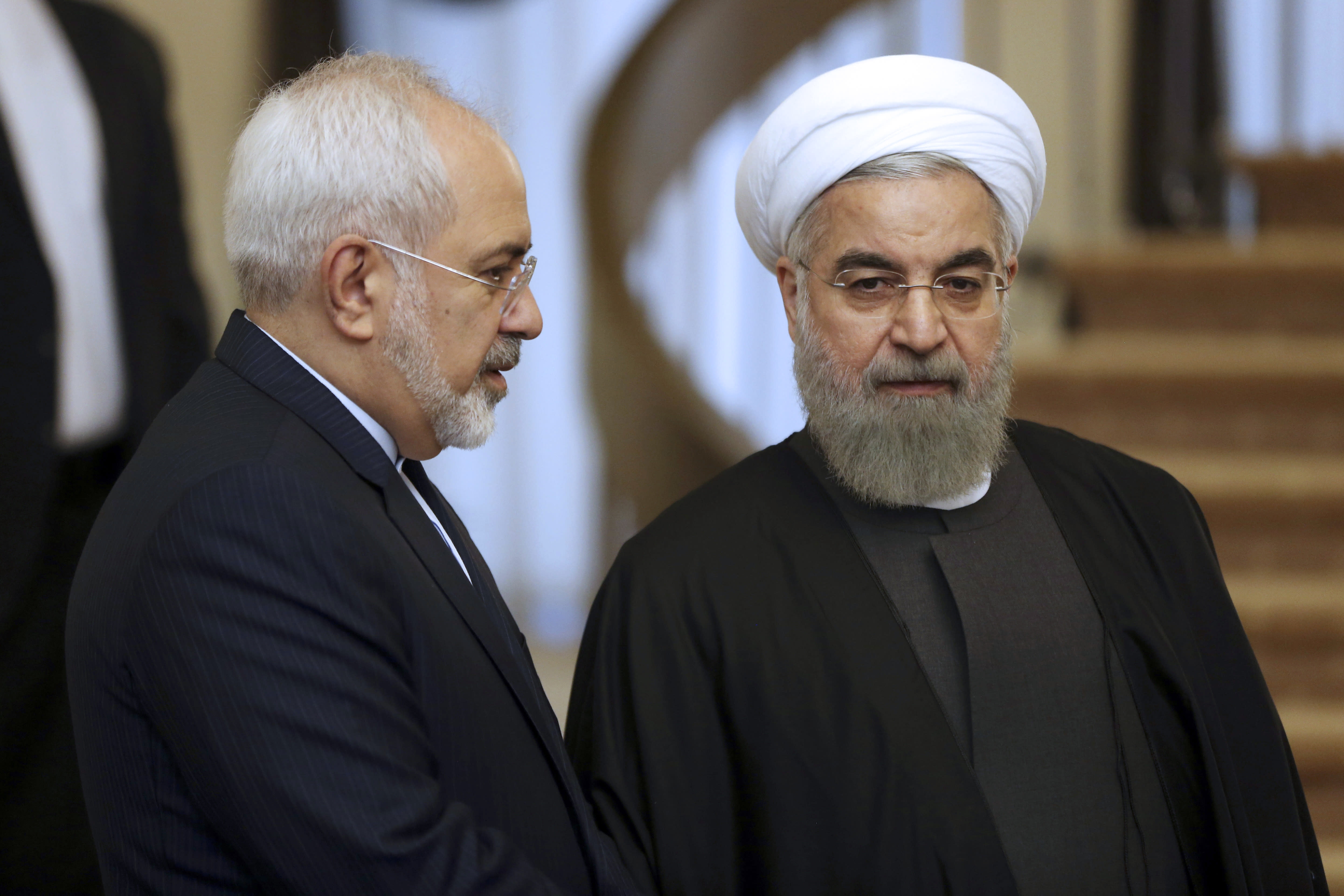 FILE - In this Nov. 24, 2015, file photo, Iranian President Hassan Rouhani, right, listens to his Foreign Minister Mohammad Javad Zarif prior to a meeting in Tehran, Iran. Rouhani is planning to make his first official visit to Iraq Monday, March 11, 2019, as he faces mounting pressure from hard-liners at home in the wake of the unravelling of the nuclear deal under the Trump administration. (AP Photo/Vahid Salemi, File)