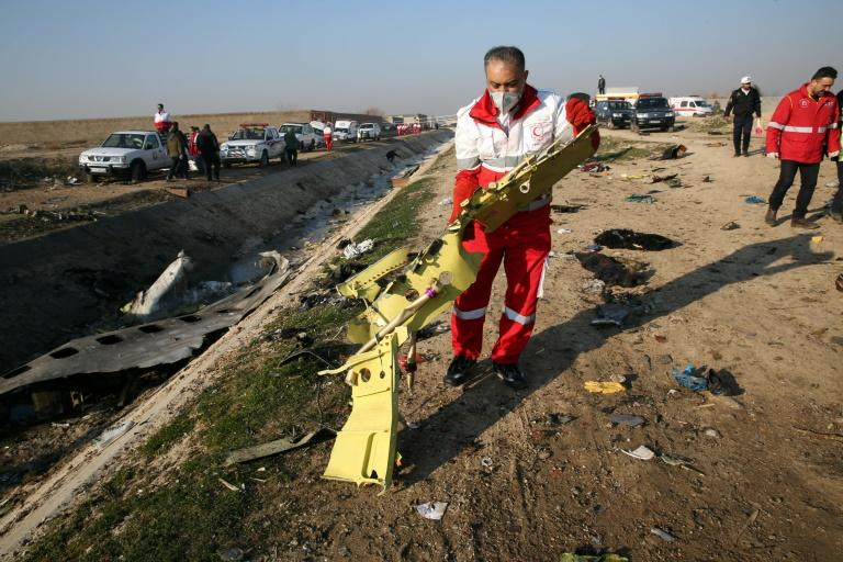 Rescue teams recover debris from a field after a Ukrainian plane carrying 176 people crashed near Tehran airport in January