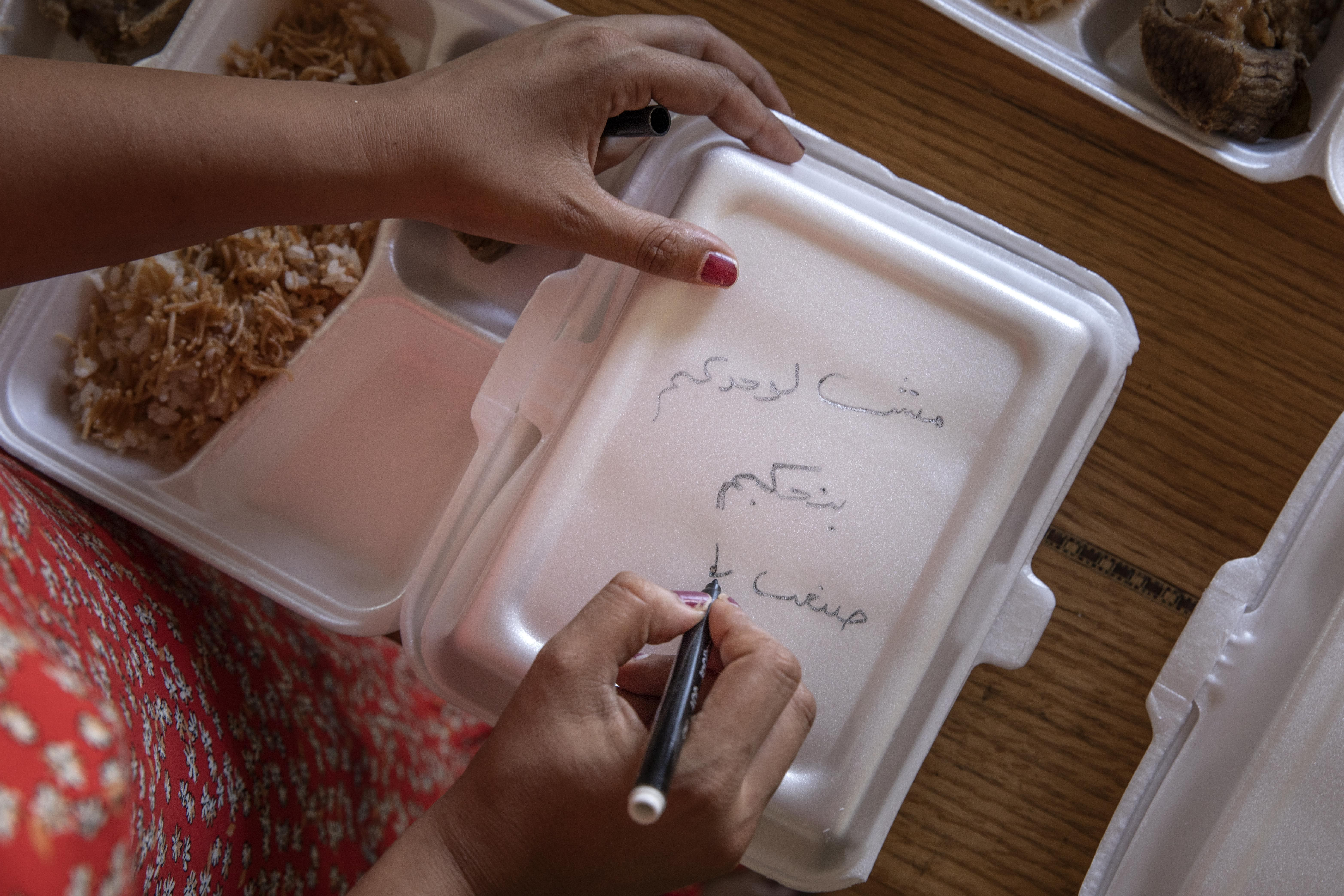 """Basma Mostafa, a 30-year-old journalist who founded an initiative that sends freshly home cooked meals to quarantined coronavirus patients, writes in Arabic, """"you are not alone, we love you,"""" on a box filled with food at a friend's apartment, in Cairo, Egypt, Saturday, July 11, 2020 photo. Mostafa, who works with others to coordinate the volunteer effort, said she got the idea of helping out when she was going through a difficult time. """"I thought that to alleviate my suffering, I can engage with the suffering of others and feel more for them,"""" she said. (AP Photo/Nariman El-Mofty)"""