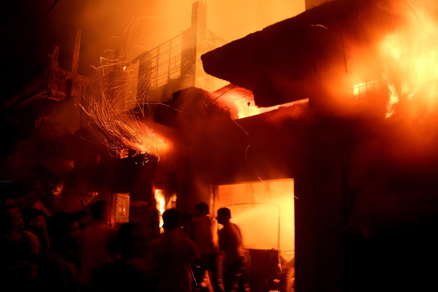 <p>Indian firefighters and local residents try to extinguish a fire at a warehouse in Bhopal, India, April 7, 2017. According to police and media reports, around 50 fire engines fought for close to eight hours to extinguish the blaze. No casualties have been reported in the incident so far. (Photo: Sanjeev Gupta/EPA) </p>