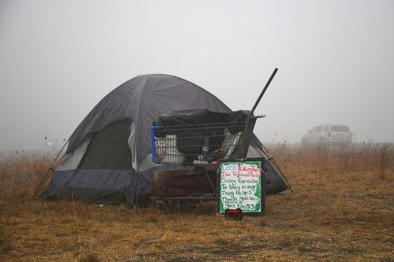 """A sign in front of a tent along the highway near Salem, Oregon on September 13, 2020 reads """"Lost Everything Due To House Fire"""""""