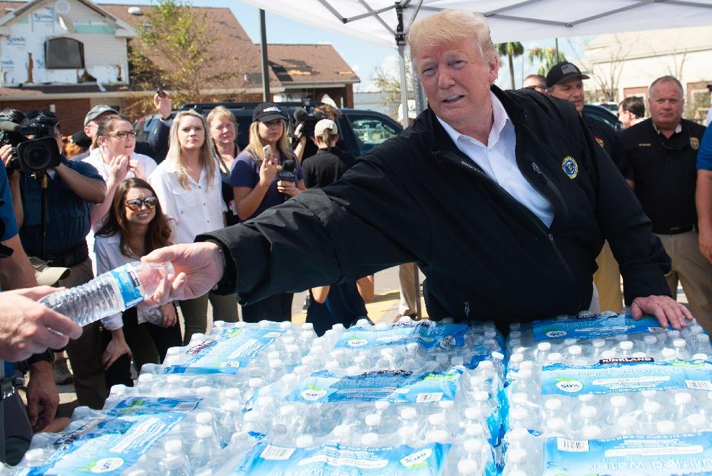 "President Donald Trump, pictured handing out bottles of water in Lynn Haven, Florida, praised Governor Rick Scott for an ""incredible job"" (AFP Photo/SAUL LOEB)"