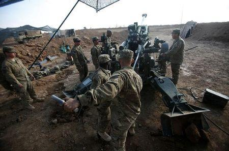 U.S. soldiers from the 2nd Brigade, 82nd Airborne Division clean the barrel of the artillery at a military base north of Mosul, Iraq