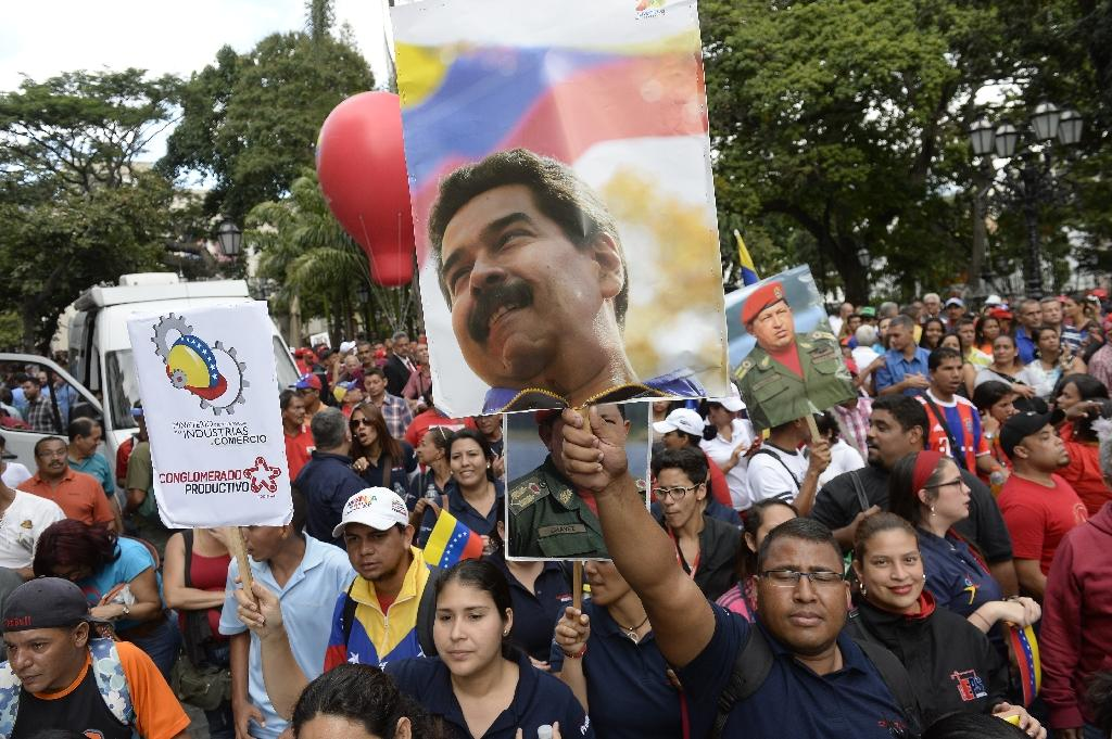 Socialist President Nicolas Maduro, (poster), and his late predecessor Hugo Chavez for years used Venezuela's big oil revenues to fund social spending programs