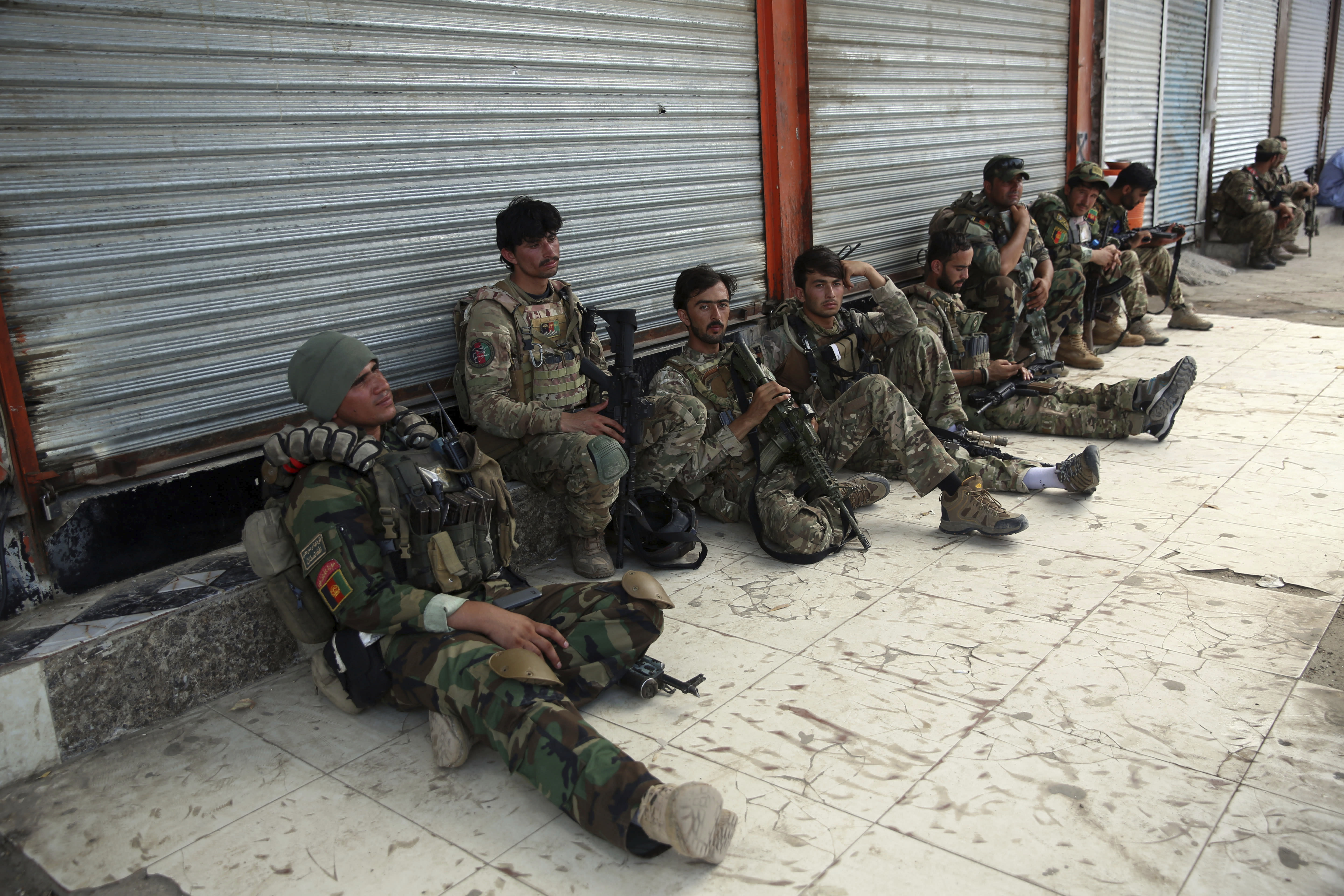 Afghan security personnels rest in front of a prison after an attack in the city of Jalalabad, east of Kabul, Afghanistan, Monday, Aug. 3, 2020. An Islamic State group attack on the prison in eastern Afghanistan holding hundreds of its members raged on Monday after killing people in fighting overnight, a local official said. (AP Photo/Rahmat Gul)