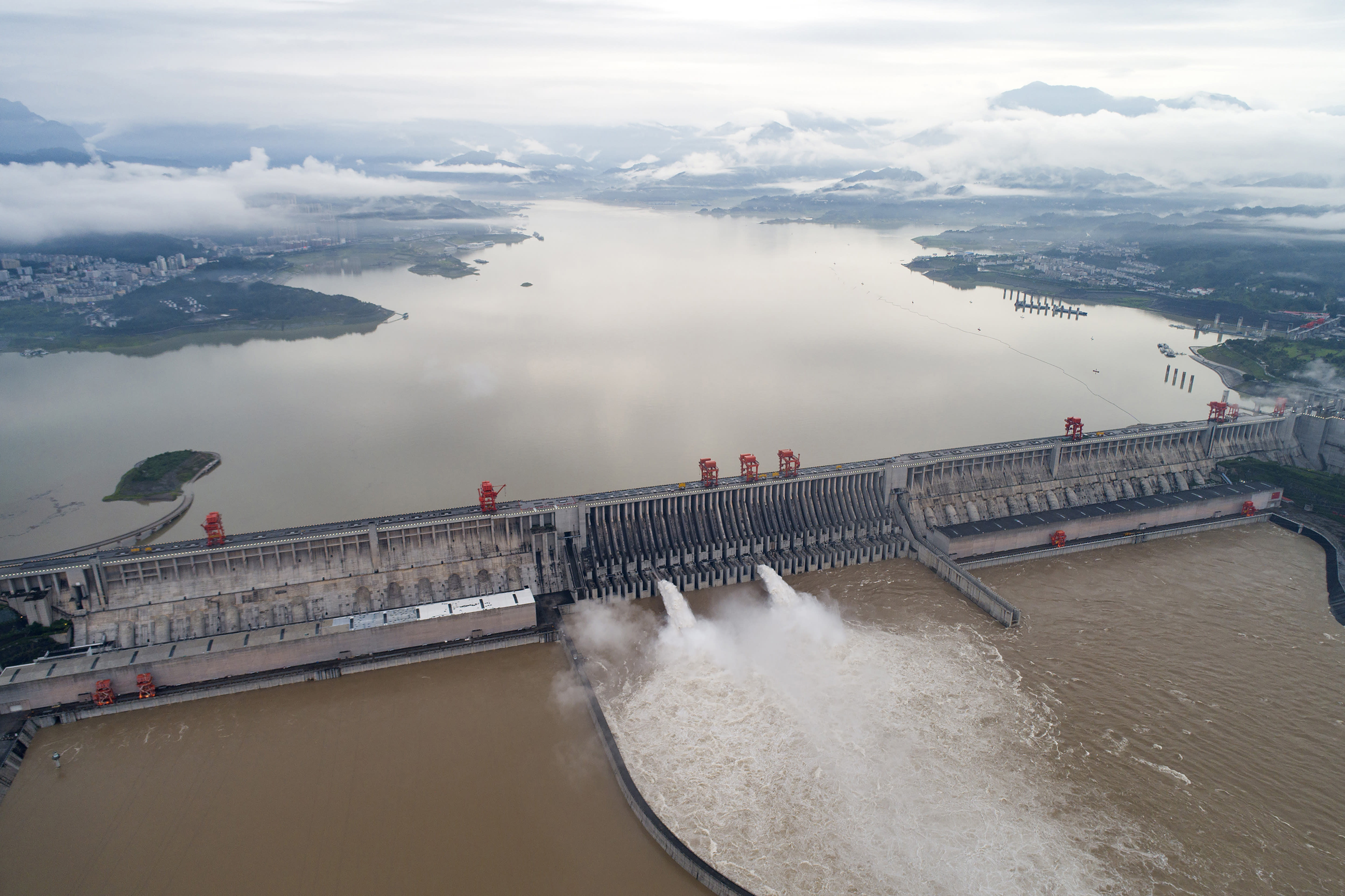 In this photo released by China's Xinhua News Agency, water flows out from sluiceways at the Three Gorges Dam on the Yangtze River near Yichang in central China's Hubei Province, Friday, July 17, 2020. Engorged with more heavy rains, China's mighty Yangtze River is cresting again, bringing fears of further destruction as seasonal floods that already have left more than a hundred people dead or missing have grown in force since last month. (Wang Gang/Xinhua via AP)