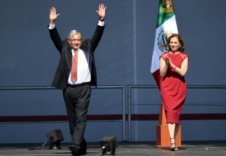 Mexican President Andres Manuel Lopez Obrador (left) waves next to his wife Beatriz Gutierrez Muller during a rally marking his first year in office at the Zocalo square in Mexico City on December 1, 2019