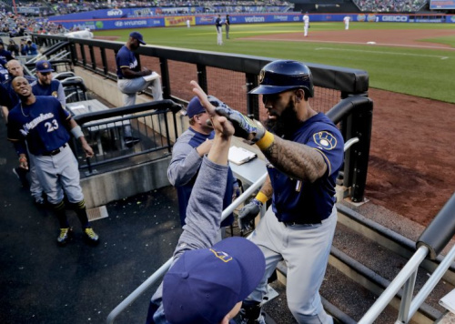 Milwaukee Brewers' Eric Thames, right, is congratulated by teammates and coaches after hitting a two-run home run against the New York Mets during the first inning of a baseball game, Wednesday, May 31, 2017, in New York. (AP Photo/Julie Jacobson)
