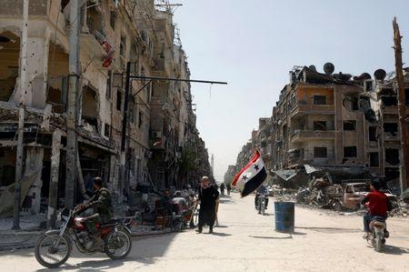 FILE PHOTO: A Syrian flag flutters along a damaged street at the city of Douma in Damascus