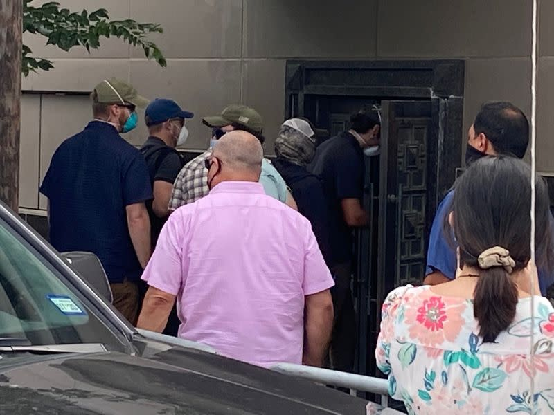 A group of people use power tools to try to pry open a rear door of the Chinese consulate in Housto