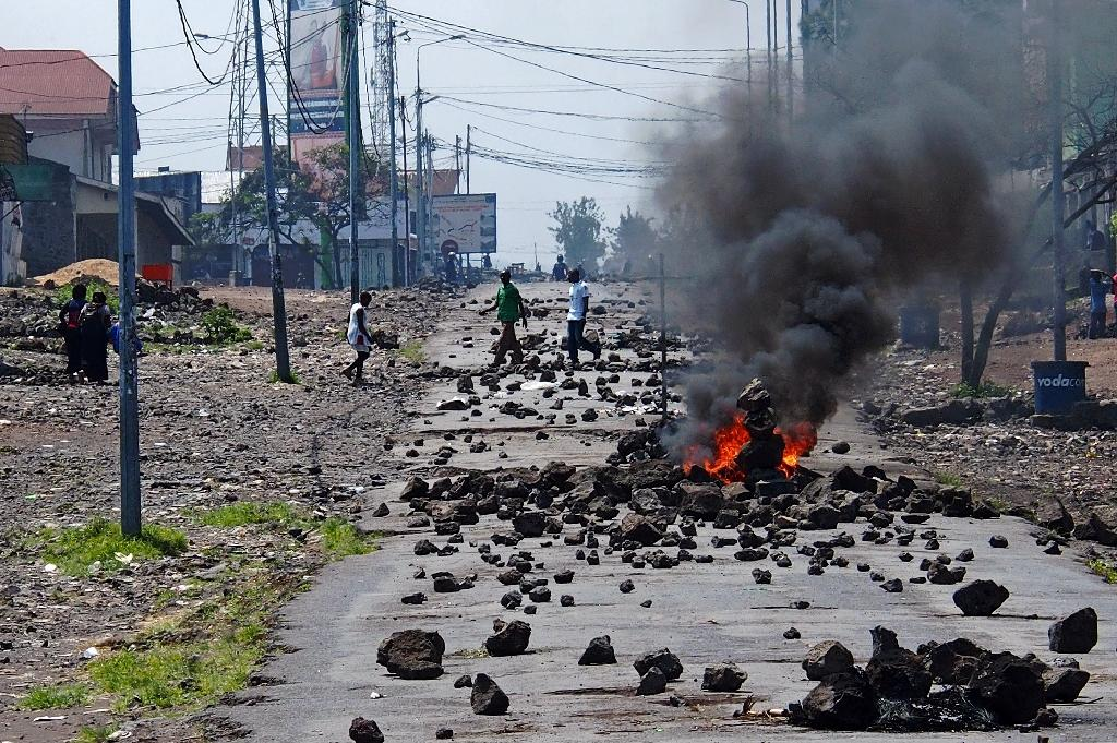 People walk past a burning barricade during a nationwide protest against long-serving President Joseph Kabila, in Goma, in May 2016 (AFP Photo/Fiston Mahamba)