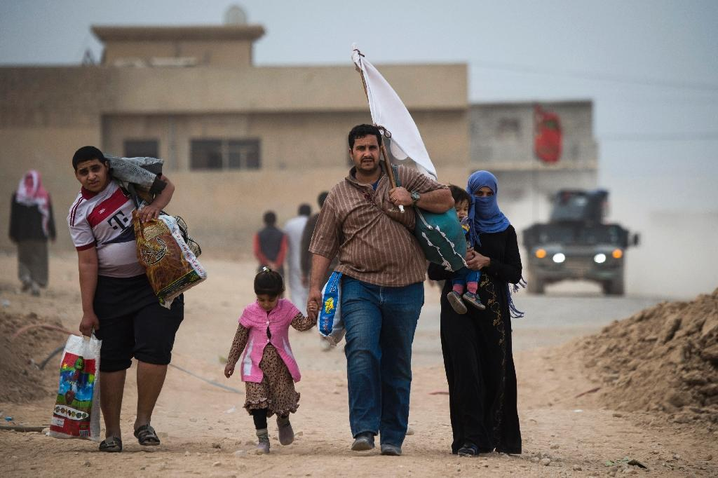 Iraqis carry white flags as they flee to an area held by government forces in the Samah neighbourhood of Mosul on November 15, 2016 (AFP Photo/Odd Andersen)