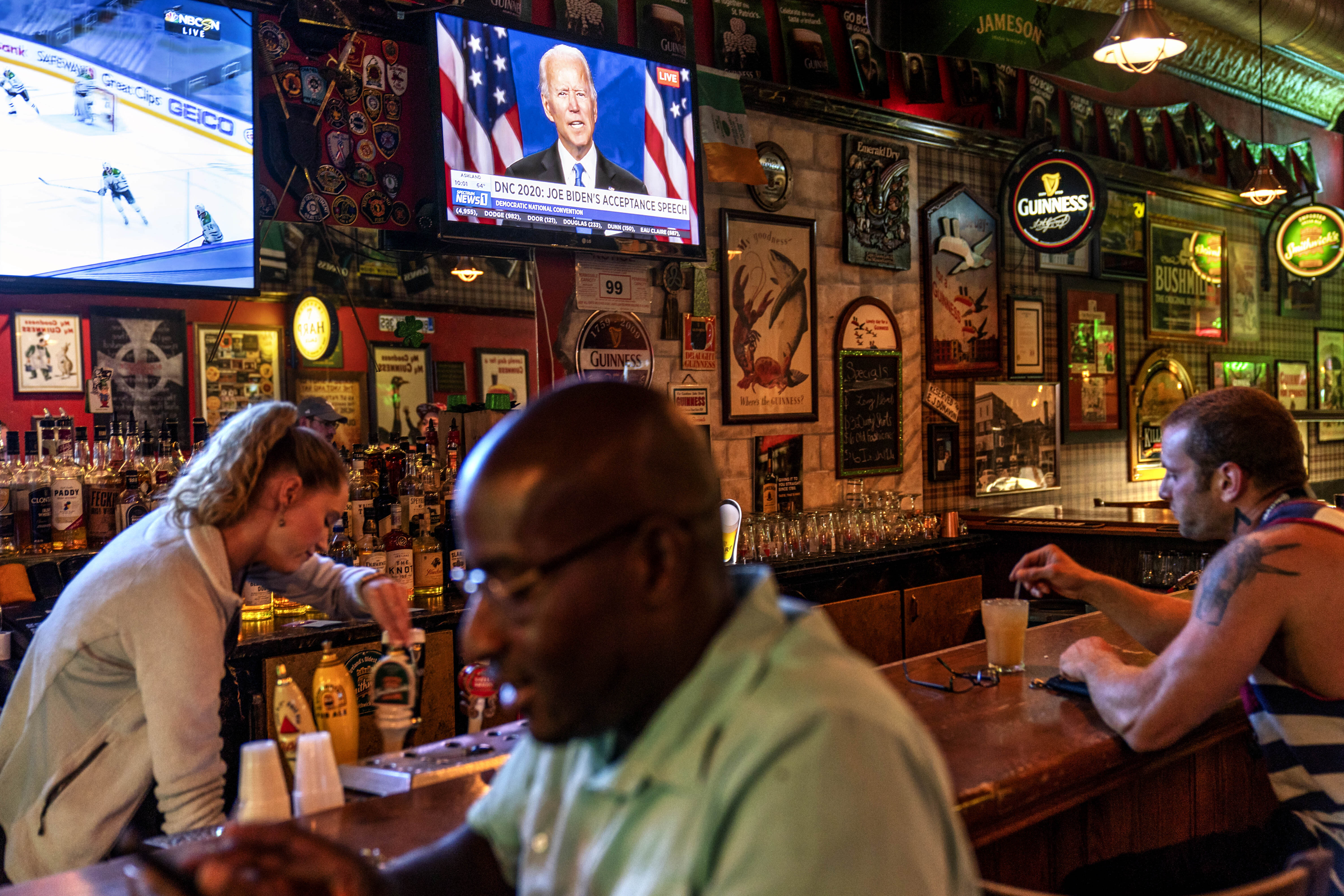 A broadcast of Democratic presidential candidate former Vice President Joe Biden speaking at the Democratic National Convention plays on a television at The Durty Leprechaun in Appleton, Wis., Aug. 20, 2020. Donald Trump won the presidency by wringing tens of thousands of votes out of small towns and medium-sized cities in Wisconsin, Michigan and Pennsylvania. How enduring the divide will be is one of the central tests of the presidential election. Will emotional ties to Trump override assessments of his job performance? (AP Photo/David Goldman)