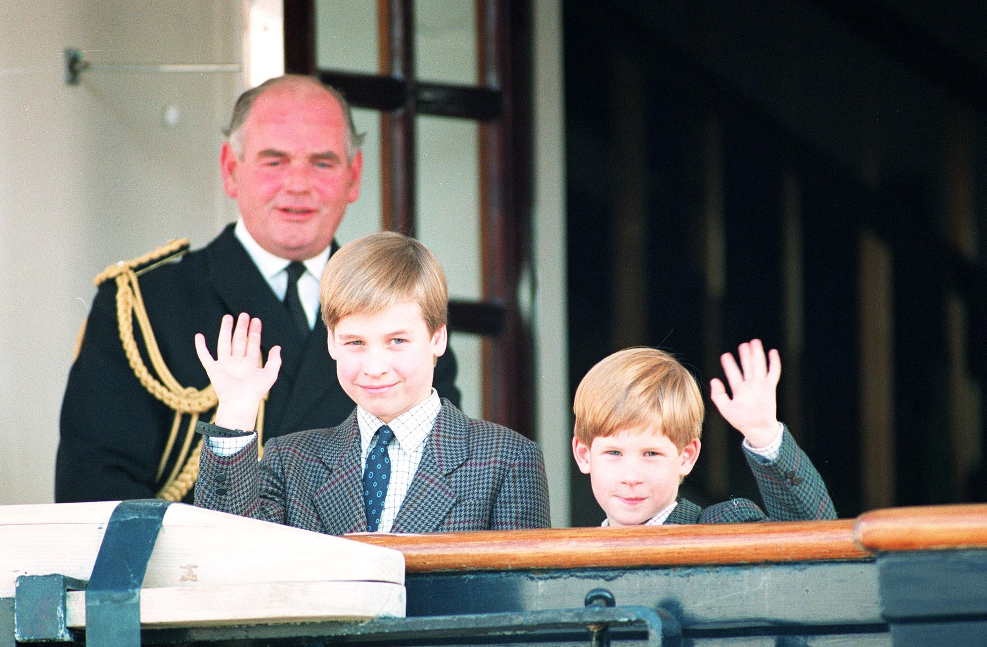 Prince William, 9, and his younger brother Prince Harry, 7, wave to photographers as they board the Royal Yacht Britannia moored on Lake Ontario alongside they Toronto waterfront. The two princes will be joind by their parents, the Prince and Princess of Wales, when they arrive in Canada for a week-long Royal visit.   (Photo by Martin Keene - PA Images/PA Images via Getty Images)