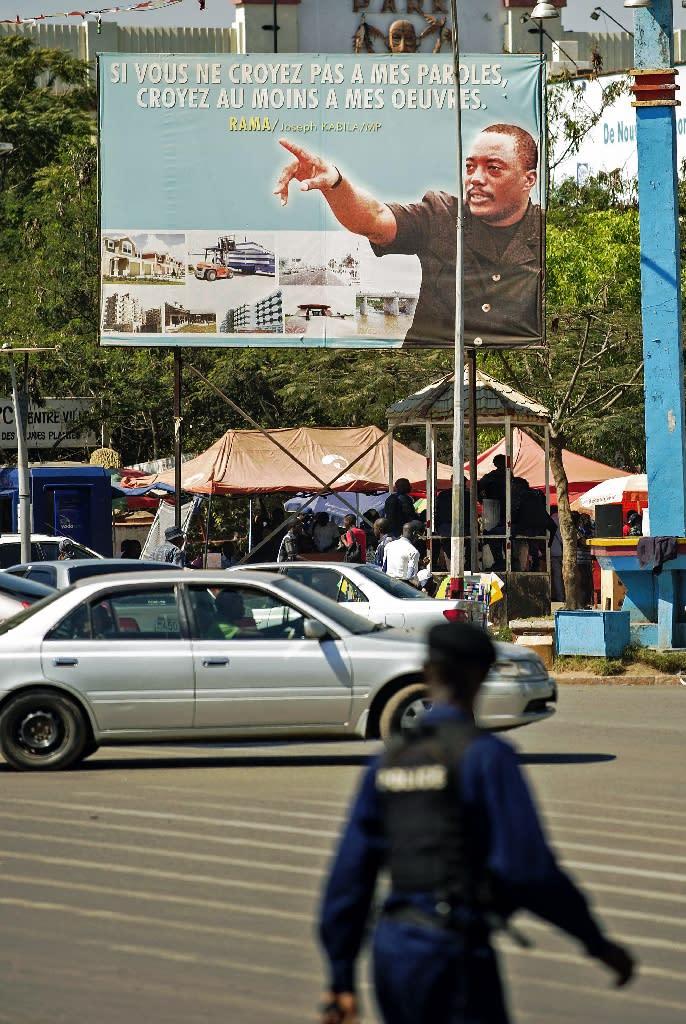 A policeman walks past a poster depicting Democratic Republic of Congo's President Joseph Kabila, in Lubumbashi on May 26, 2016 (AFP Photo/Junior Kannah)