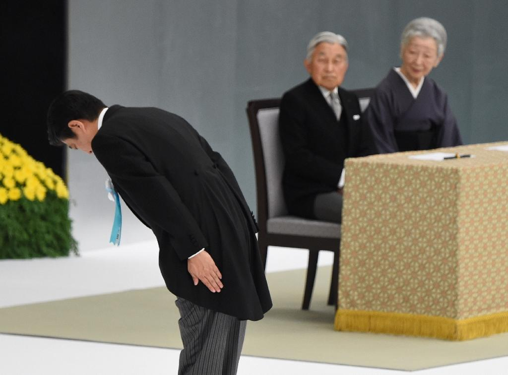 Japanese Prime Minister Shinzo Abe (L) bows to an altar beside Emperor Akihito and Empress Michiko during the official annual memorial service for war victims, in Tokyo, on August 15, 2016 (AFP Photo/Toru Yamanaka)