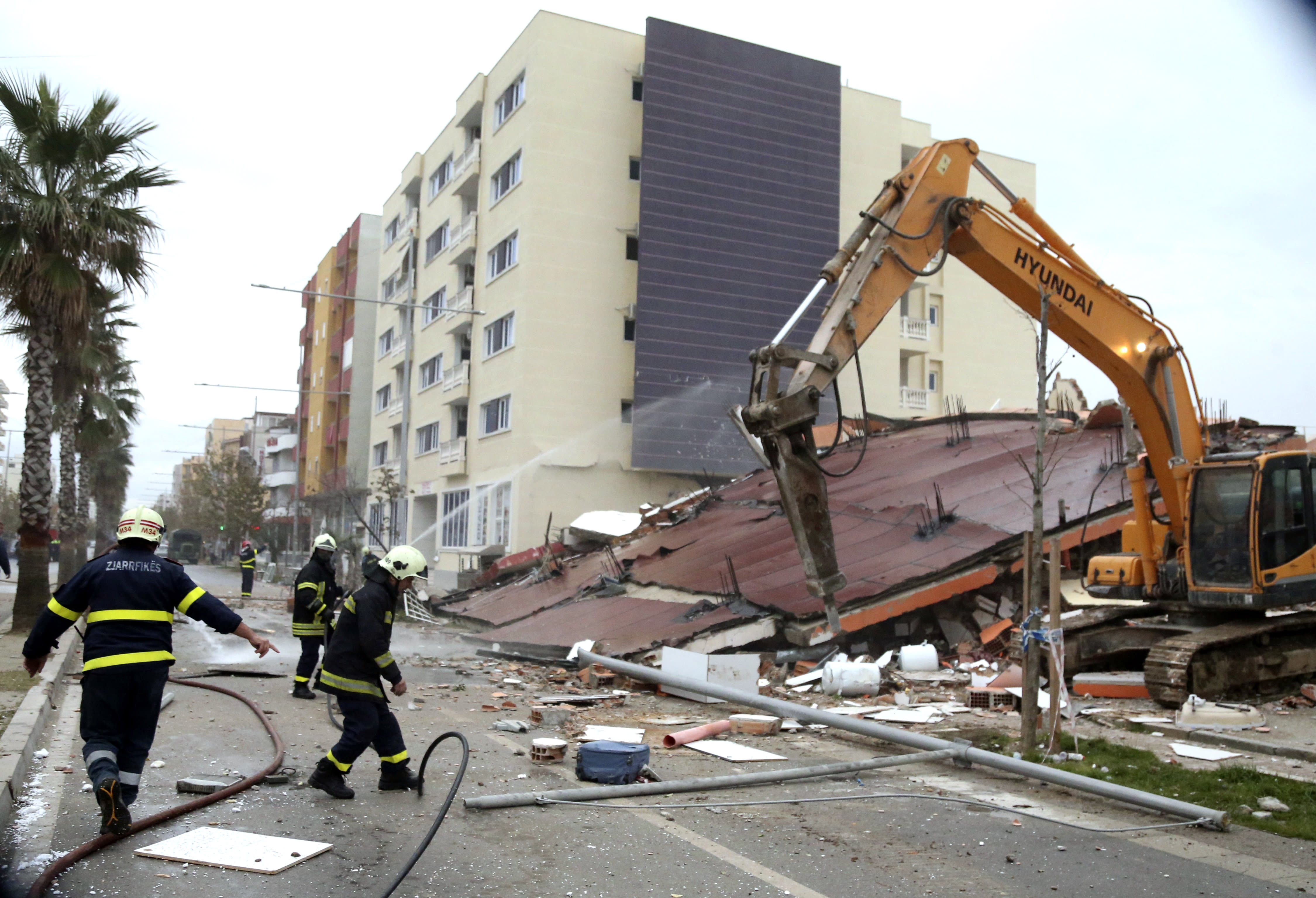 Firefighters clean the road from debris after a remote-controlled explosion to demolish a building in the western port city of Durres, Albania, Tuesday, Dec. 3, 2019. A remote-controlled explosion has demolished the six-storied building considered threatening after being damaged from the 6.4 magnitude earthquake in Albania. A quake a week ago killed 51 persons, injured more than 3,000 people, and damaged more than 11,000 buildings. (AP Photo/Hektor Pustina)