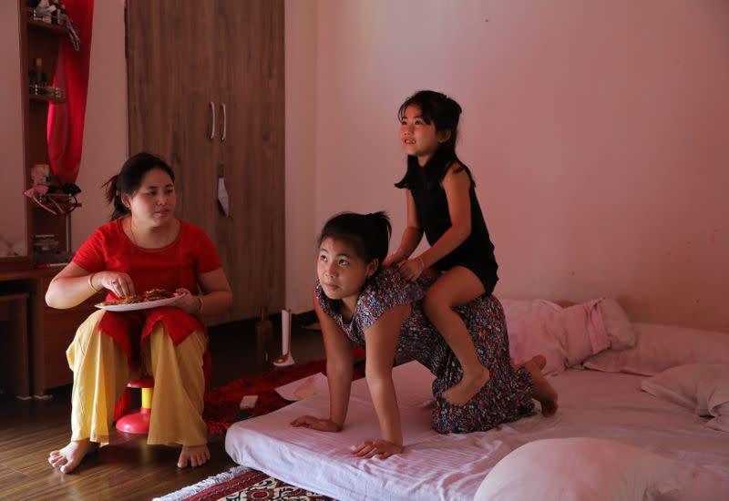Licypriya Kangujam plays with her sister Irina Kangujam as their mother Bidyarani Devi Kangujam Ongbi looks on inside their house in Noida