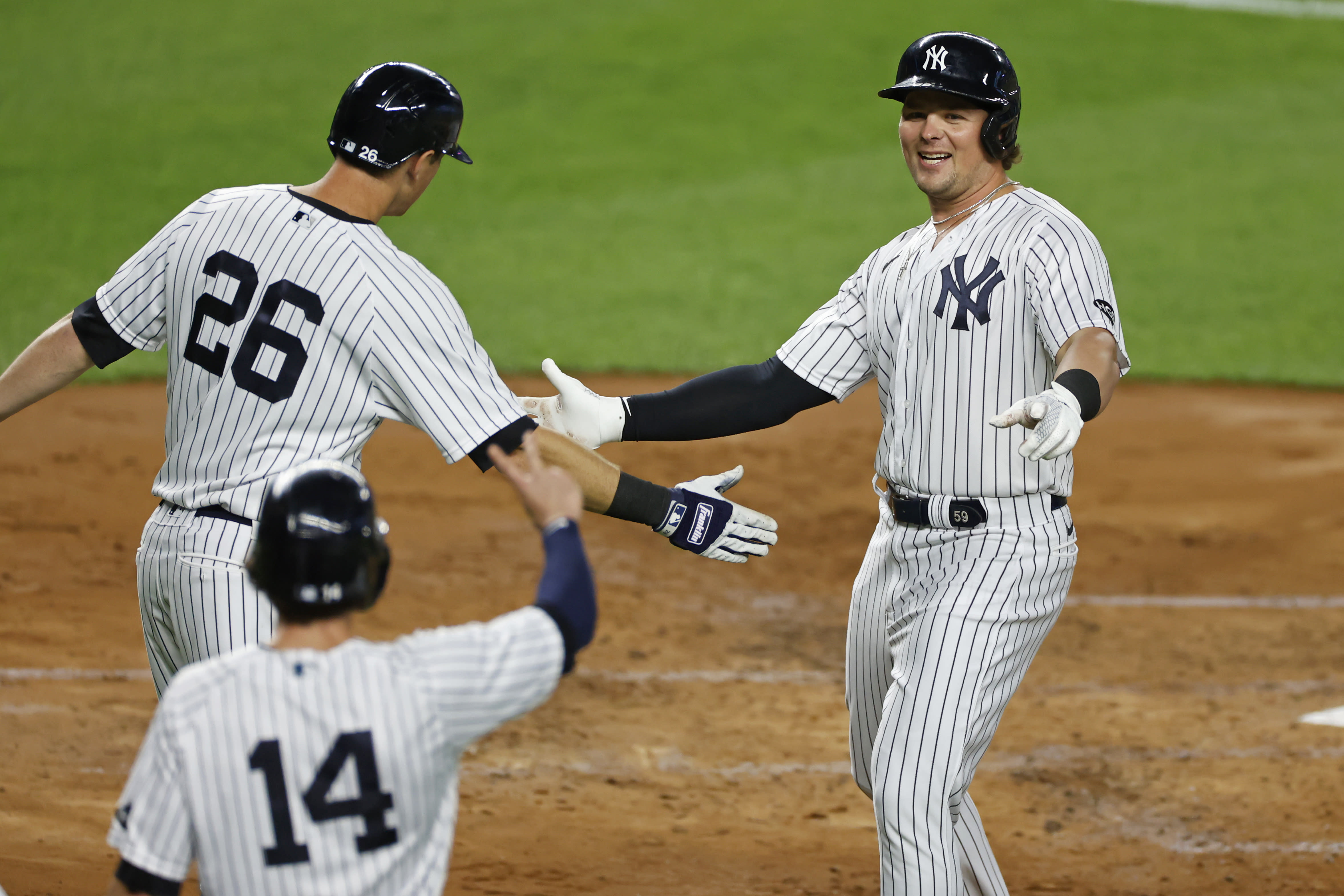 New York Yankees' Luke Voit celebrates hitting a three-run home run with DJ LeMahieu (26) and Tyler Wade (14) during the second inning of a baseball game against the Toronto Blue Jays on Tuesday, Sept. 15, 2020, in New York. (AP Photo/Adam Hunger)