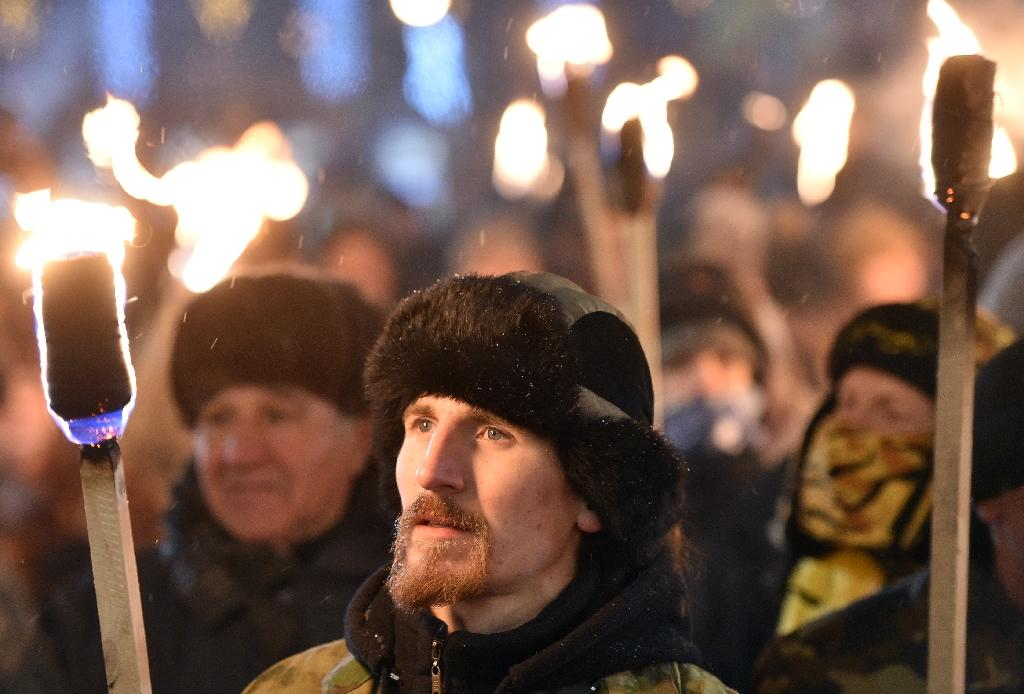 Nationalists hold torches during a march in Kiev on January 1, 2016, as they mark the 107th anniversary of the birth of Ukrainian politician Stepan Bandera (AFP Photo/Genya Savilov)