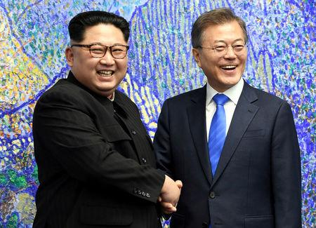South Korean President Moon Jae-in shakes hands with North Korean leader Kim Jong Un during their meeting at the Peace House