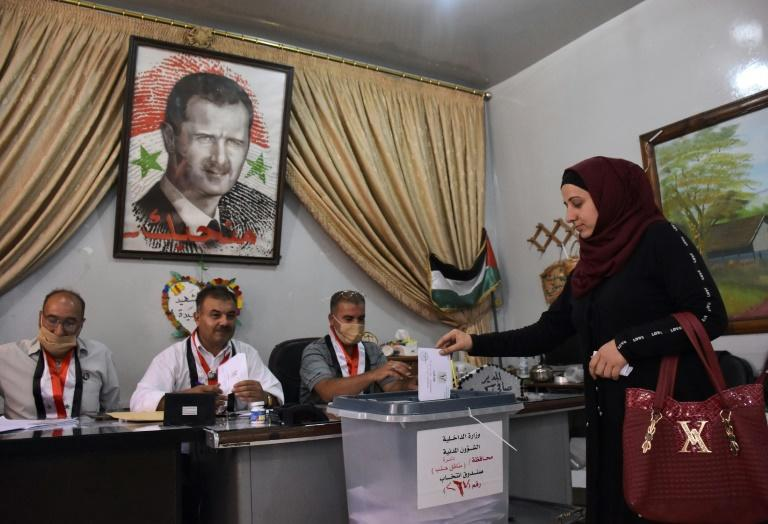 A Syrian woman casts her ballot at a polling station in the Nubl neighbourhood of Aleppo on July 19, 2020, during the parliamentary elections, in which President Bashar al-Assad's party and allies took 177 seats out of 250
