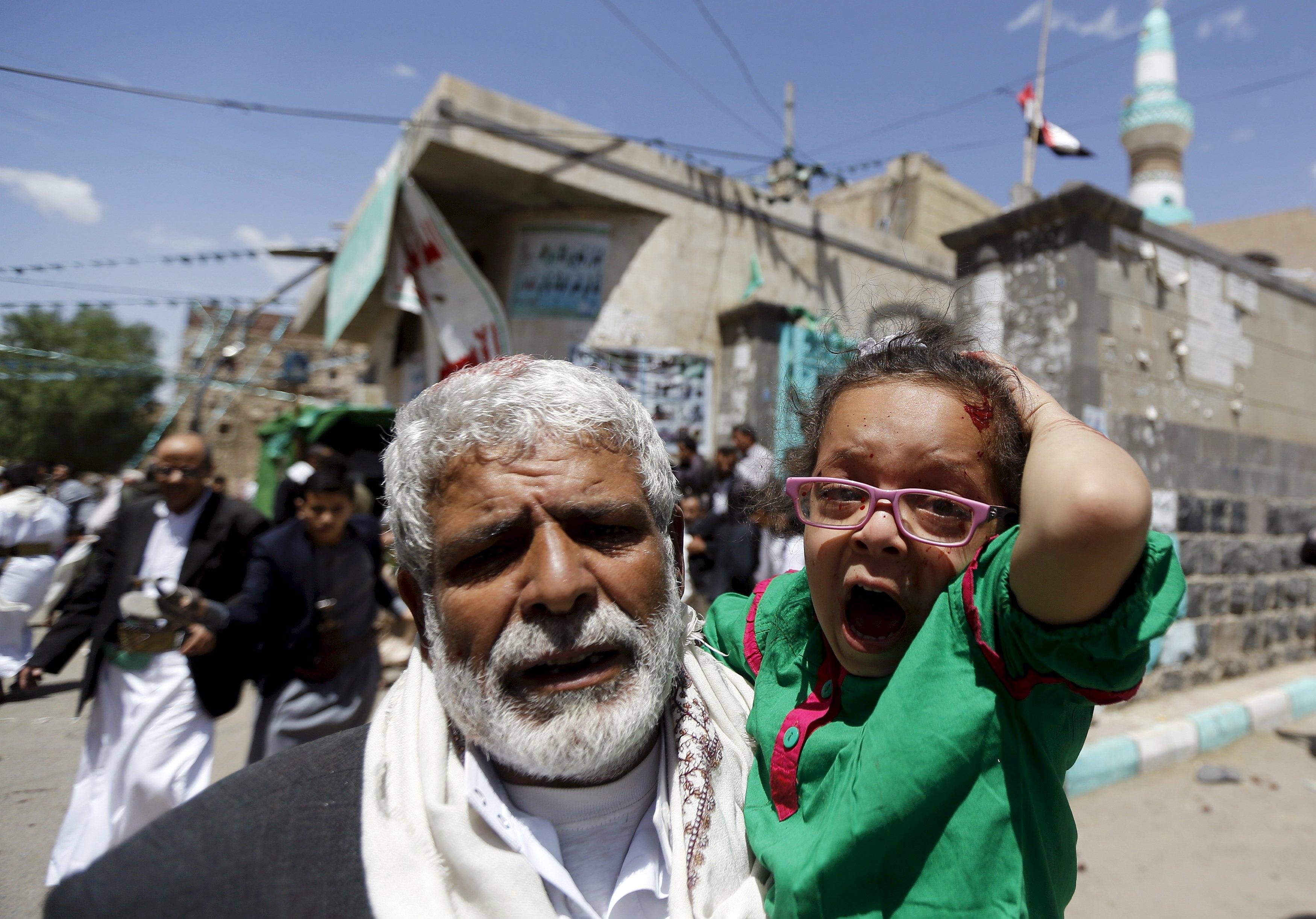 An injured girl reacts as she is carried by a man out of a mosque which was attacked by a suicide bomber in Sanaa March 20, 2015. At least 16 people were killed when suicide bombers blew themselves up in two mosques in the Yemeni capital Sanaa on Friday during noon prayers, medical sources told Reuters. The mosques are known to be used mainly by supporters of the Shi'ite Muslim Houthi group which has seized control of the government. REUTERS/Khaled Abdullah