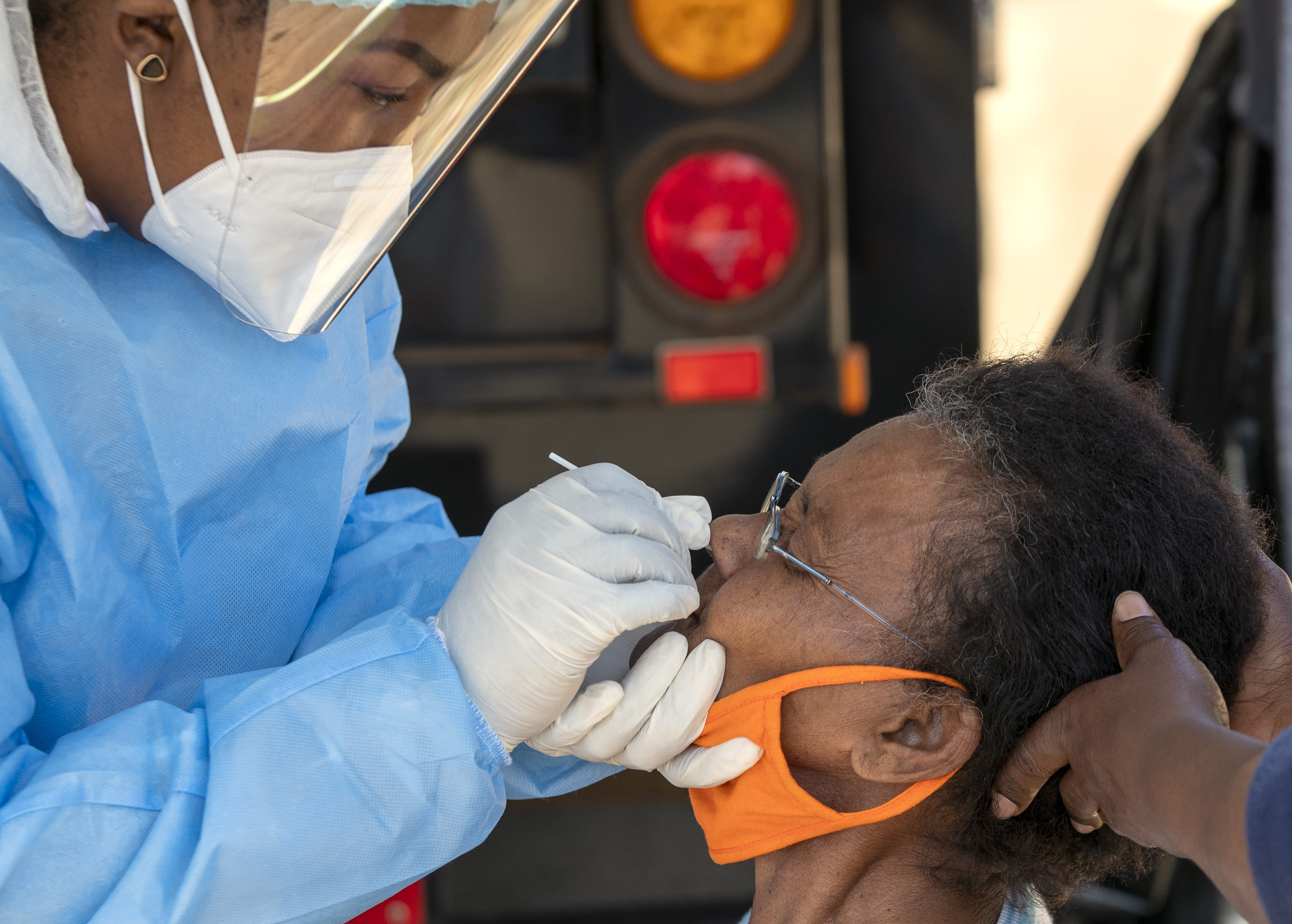 An woman reacts as a heatlh worker collects a sample for coronavirus testing during the screening and testing campaign aimed to combat the spread of COVID-19, in Eldorado Park outside of Johannesburg, South Africa, Monday, Aug. 3, 2020. (AP Photo/Themba Hadebe)