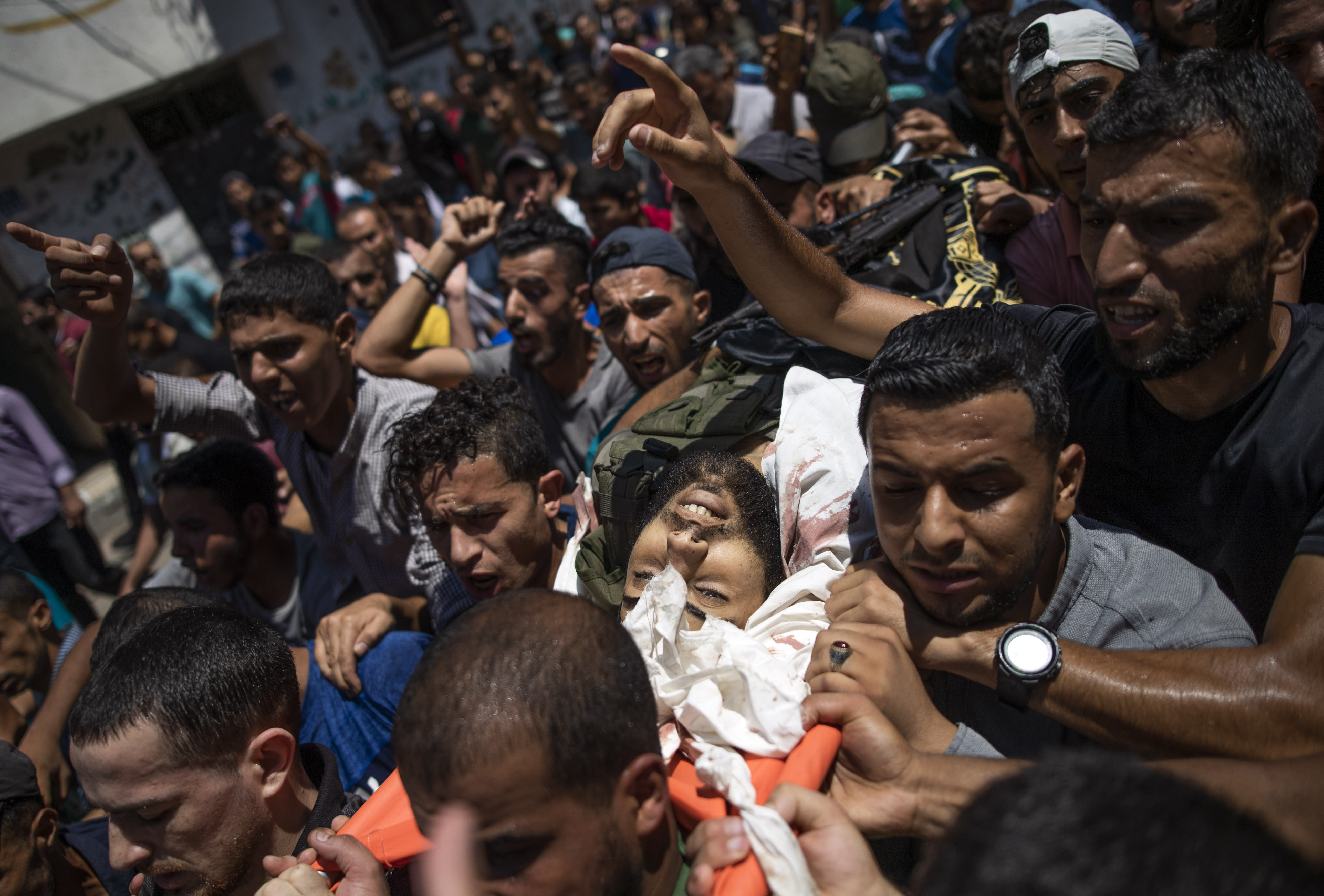 Mourners chant angry slogans as they carry the body of Islamic Jihad militant, Mahmoud al-Walayda, 24, during his funeral in the Jabaliya refugee camp, northern Gaza Strip, Sunday, Aug. 18, 2019. Gaza's Health Ministry said Israeli troops killed three Palestinians and severely wounded a fourth near the heavily guarded perimeter fence. The Israeli military said Sunday that a helicopter and a tank fired at a group of armed suspects near the fence overnight. (AP Photo/Khalil Hamra)