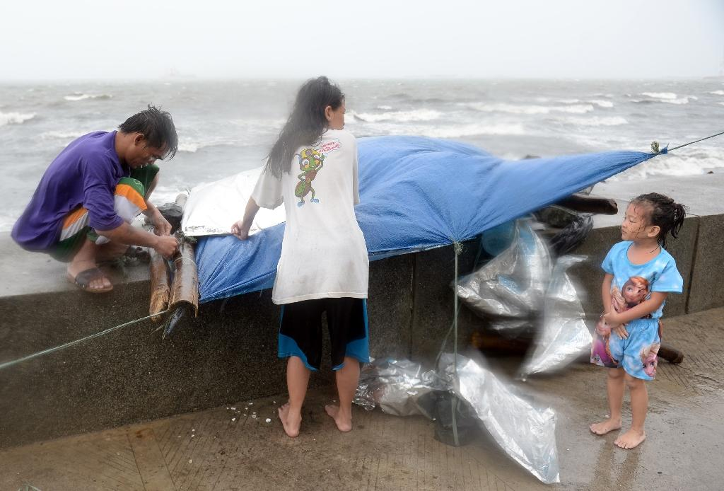 A family fix their temporary shelter during heavy wind and rains brought on by Powerful Typhoon Koppu along Roxas boulevard in Manila on October 18, 2015 (AFP Photo/Ted Aljibe)