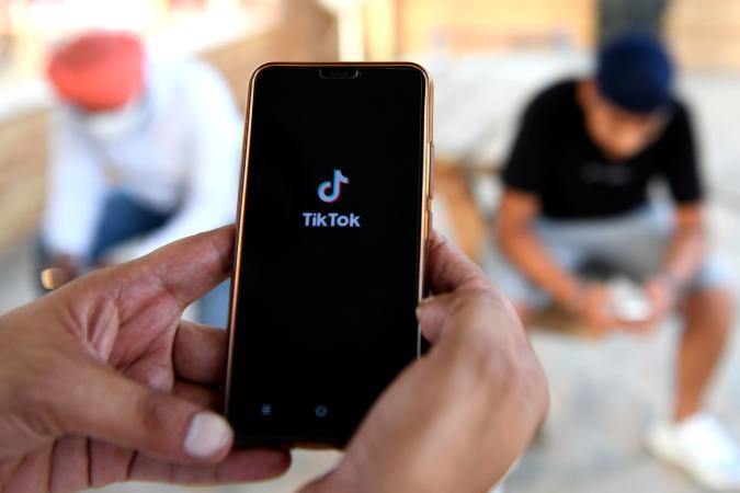 """Indian mobile users browses through the Chinese owned video-sharing 'Tik Tok' app on a smartphones in Amritsar on June 30, 2020. - TikTok on June 30 denied sharing information on Indian users with the Chinese government, after New Delhi banned the wildly popular app citing national security and privacy concerns. """"TikTok continues to comply with all data privacy and security requirements under Indian law and have not shared any information of our users in India with any foreign government, including the Chinese Government,"""" said the company, which is owned by China's ByteDance. (Photo by NARINDER NANU / AFP) (Photo by NARINDER NANU/AFP via Getty Images)"""