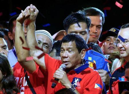 "Philippine presidential candidate and Davao city mayor Rodrigo 'Digong' Duterte raised his arm by a supporter during a ""Miting de Avance"" before the national elections at Rizal park in metro Manila"