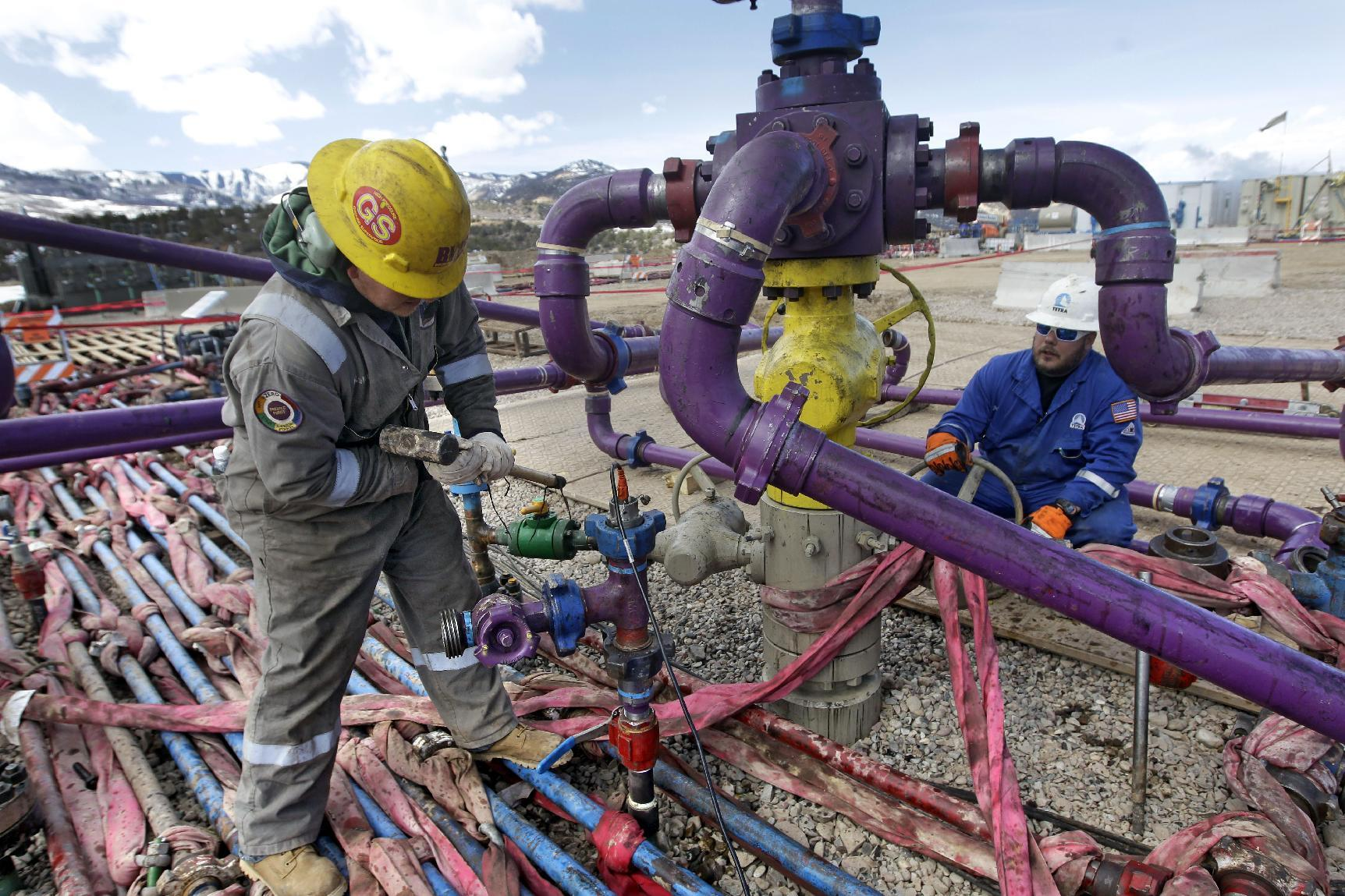 """FILE - In this March 29, 2013 file photo, workers tend to a well head during a hydraulic fracturing operation at an Encana Oil & Gas (USA) Inc. gas well outside Rifle, in western Colorado. The Obama administration is proposing a rule that would require companies that drill for oil and natural gas on federal lands to publicly disclose chemicals used in hydraulic fracturing operations. The new """"fracking"""" rule replaces a draft proposed last year that was withdrawn amid industry complaints that federal regulation could hinder an ongoing boom in natural gas production. (AP Photo/Brennan Linsley, File)"""