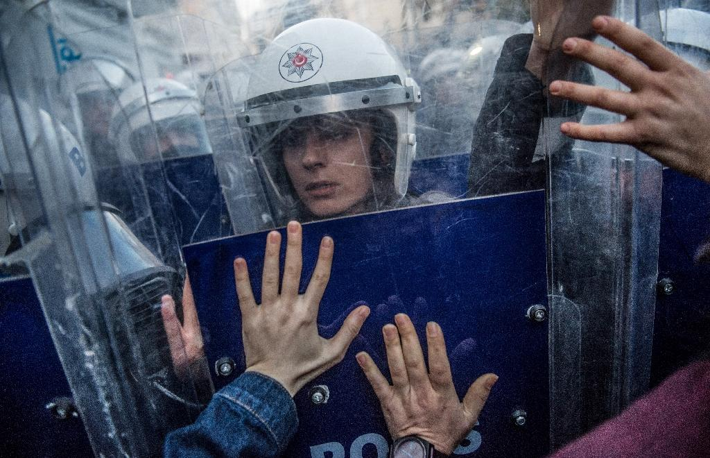 Male and female riot police used shields and tear gas to stop the march moving through central Istanbul (AFP Photo/BULENT KILIC)