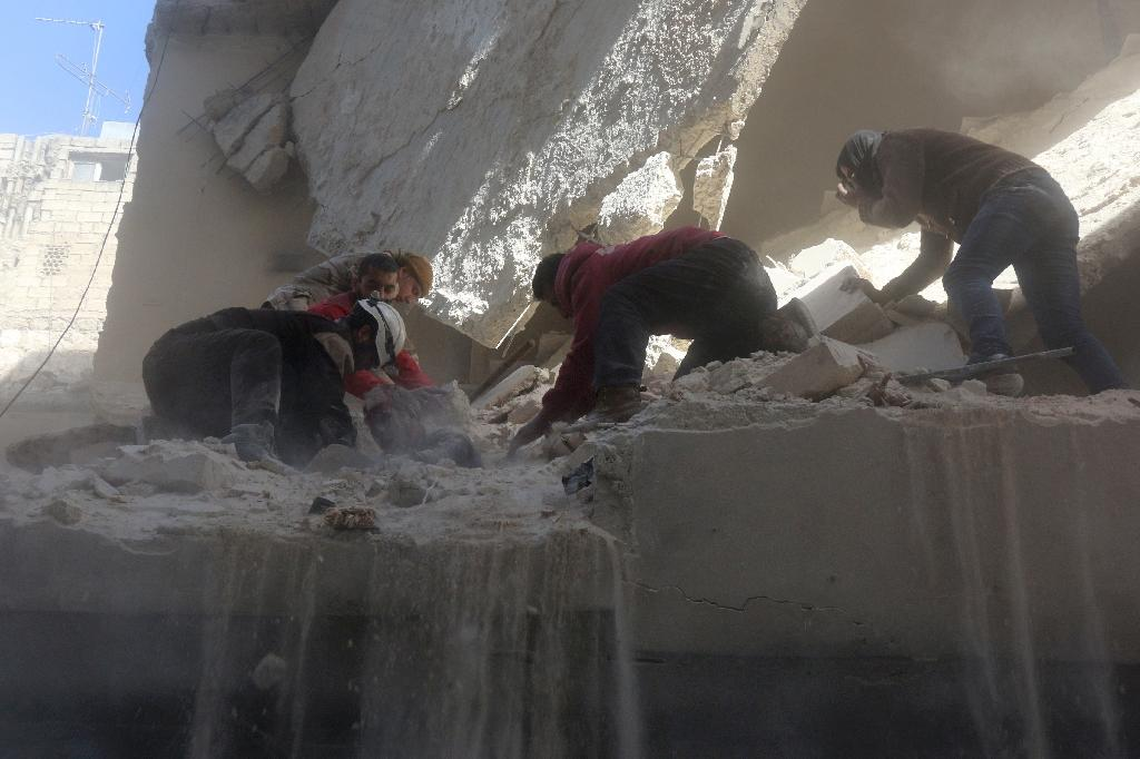Syrian rescue workers and residents try to pull a man out from under the rubble of a building following a reported air strike on the rebel-held neighbourhood of Salhin in the northern city of Aleppo (AFP Photo/Thaer Mohammed)