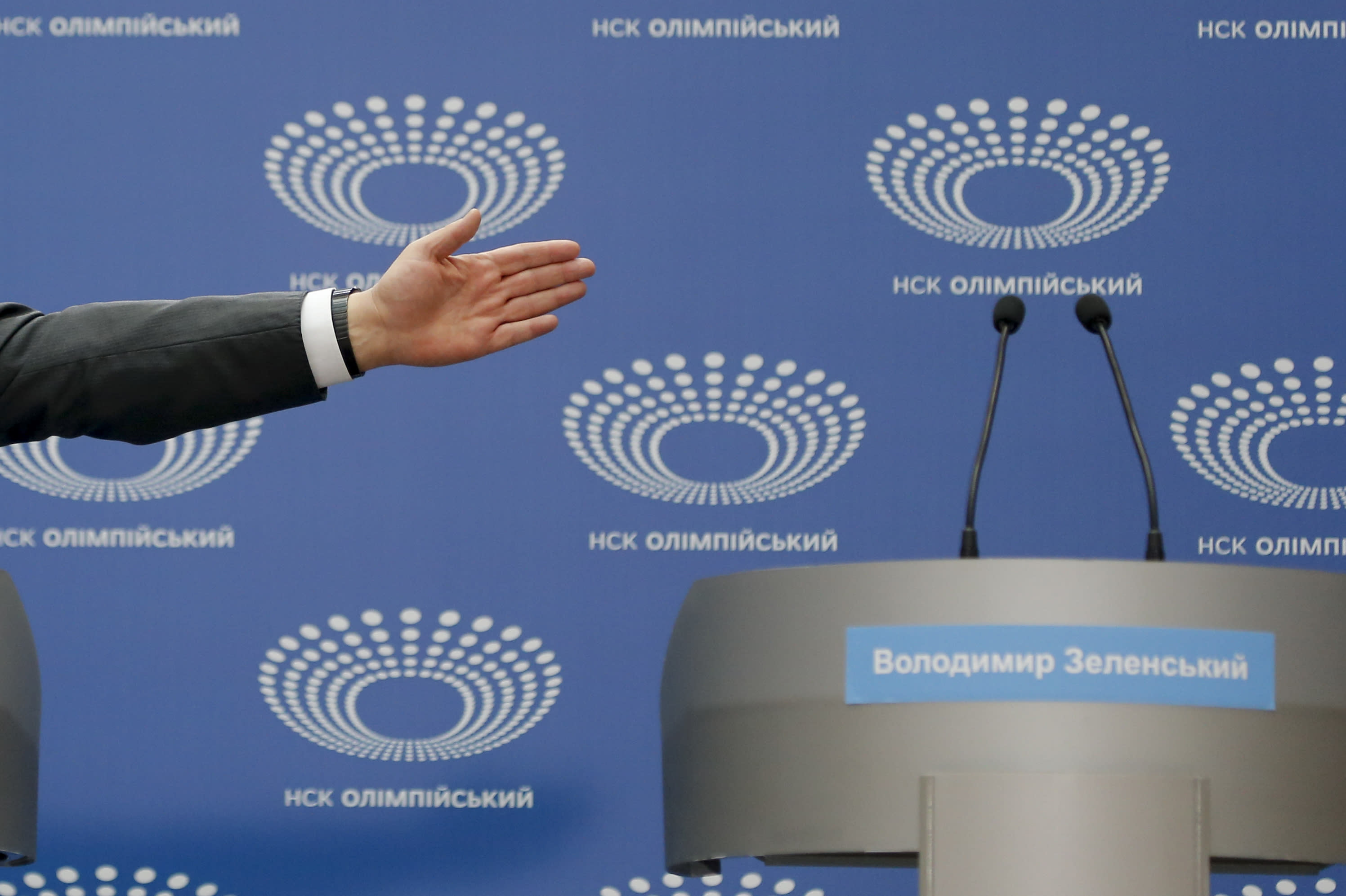Ukrainian President Petro Poroshenko gestures toward a tribune with Volodymyr Zelenskiy's name written on it, as he answers a journalist's question ahead of the presidential elections on April 21, at the Olympic stadium in Kiev, Ukraine, Sunday, April 14, 2019. Zelenskiy, who's never held office, challenged Poroshenko to take part in a debate in the stadium two days before the election, but Poroshenko wanted it to be held Sunday. (AP Photo/Efrem Lukatsky)
