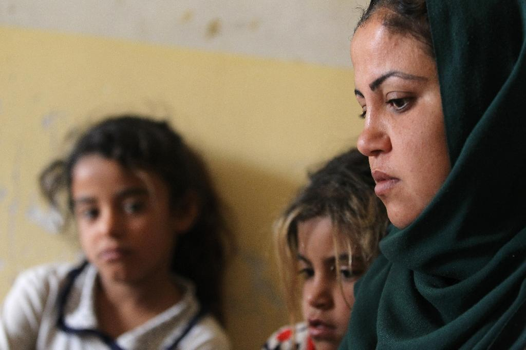 """Alaa Hamza, a 28-year-old mother sits with her children in their rented home in Hawija, 45 kilometres west of Kirkuk in northern Iraq. """"My son has epilepsy, autism, and no ID,"""" she says. (AFP Photo/AHMAD AL-RUBAYE)"""