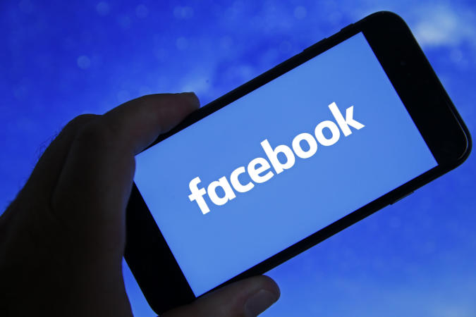 """PARIS, FRANCE - OCTOBER 06: In this photo illustration, the Facebook logo is displayed on the screen of an iPhone on October 06, 2021 in Paris, France. Frances Haugen, a former employee of the Facebook social network created by Mark Zuckerberg, told the US Senate on October 05 that Facebook was prioritizing its profits at the expense of security and the impact of the social network on young users. To support her claims, Frances Haugen draws on her two-year experience as a product manager at Facebook and on the thousands of documents she took with her last spring, grouped together under the name of """"Facebook Files """". (Photo illustration by Chesnot/Getty Images)"""