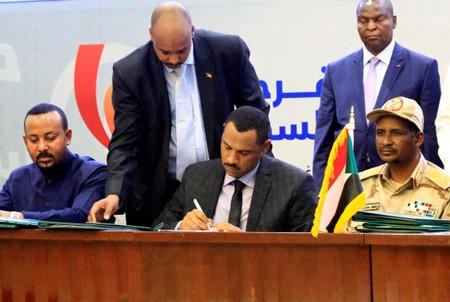 Deputy Chairman of the Sudanese Transitional Military Council, Mohamed Hamdan Dagalo, and Sudan's opposition alliance coalition's leader Ahmad al-Rabiah, sign a power sharing deal, as Ethiopia's Prime Minister Abiy Ahmed witnesses, in Khartoum
