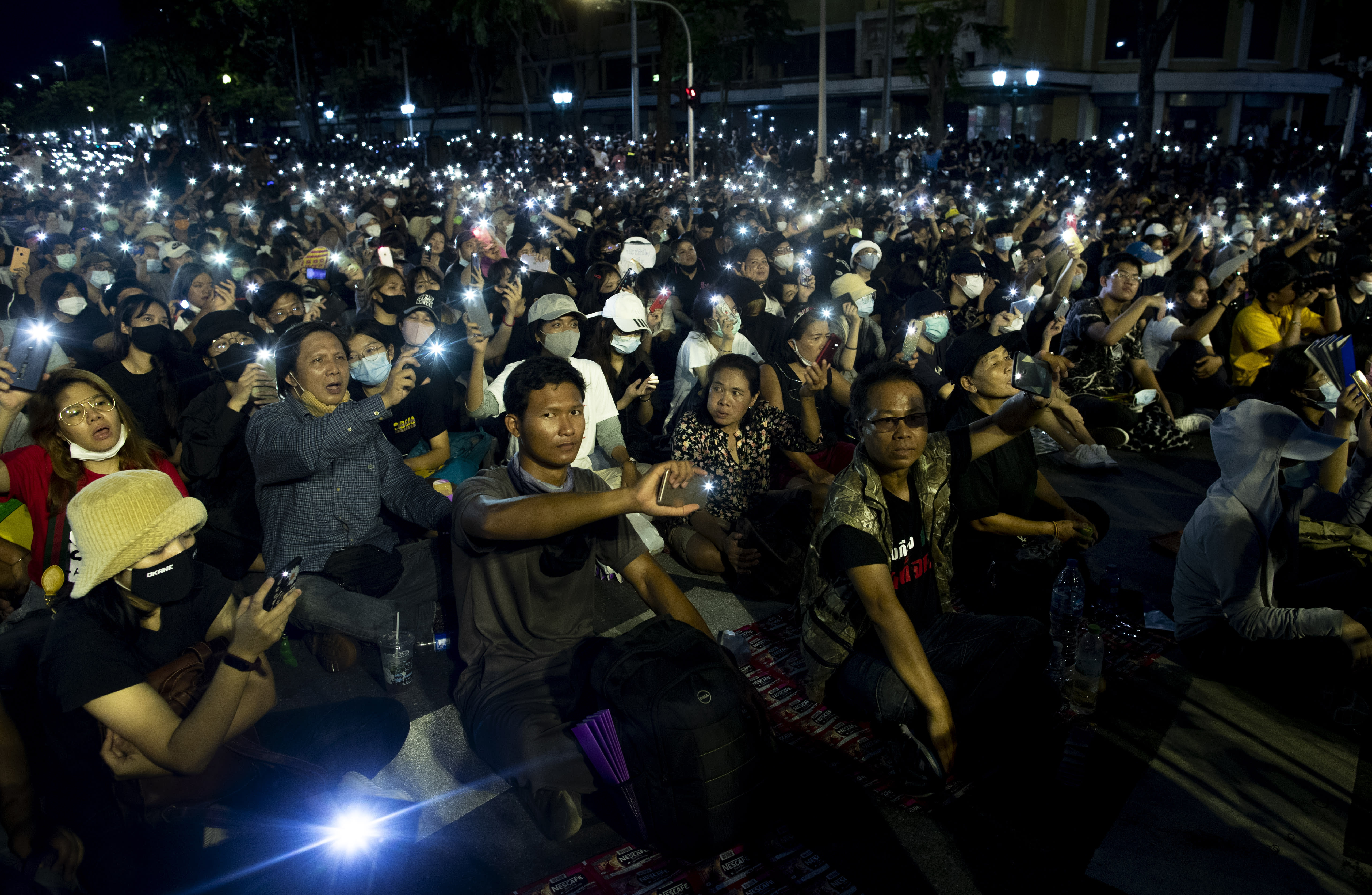 Pro-democracy activities display mobile phones with flash lights on during a protest at Democracy Monument in Bangkok, Thailand, Sunday, Aug, 16, 2020. A two-day rally planned for this weekend is jangling nerves in Bangkok, with apprehension about how far student demonstrators will go in pushing demands for reform of Thailand's monarchy and how the authorities might react. More than 10,000 people are expected to attend the Saturday-Sunday event. (AP Photo/Gemunu Amarasinghe)