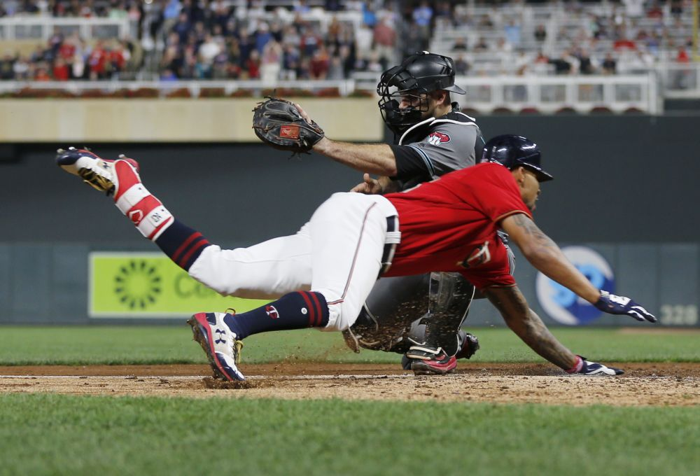 Byron Buxton beats the tag by Diamondbacks catcher Chris Iannetta to complete an inside-the-park home run. (AP)