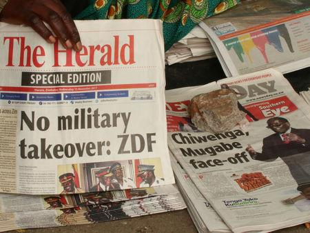 A vendor picks up a copy of a special edition of the state-owned daily newspaper The Herald in Harare, Zimbabwe November 15, 2017. REUTERS/Philimon Bulawayo