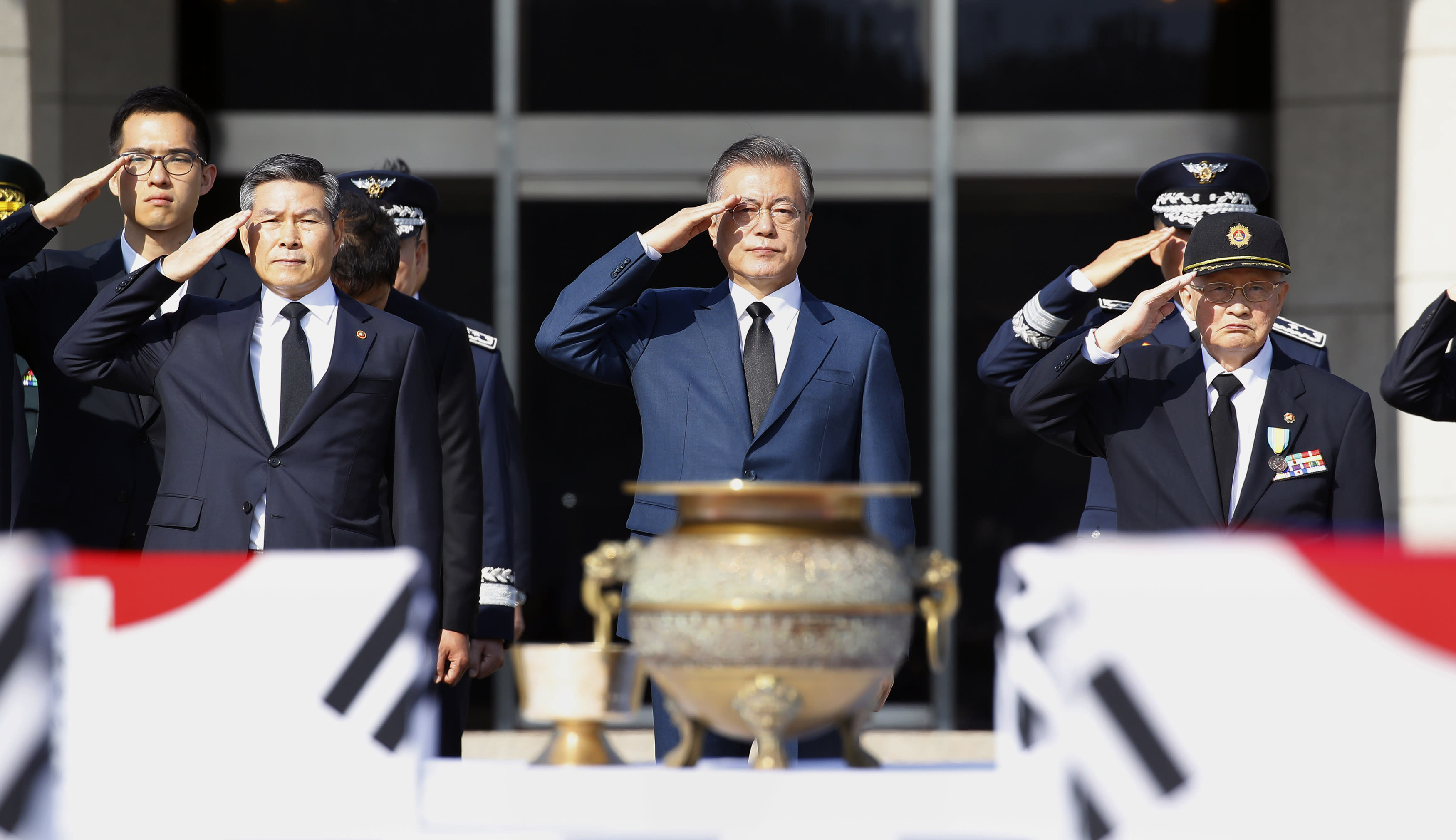 South Korean President Moon Jae-in, center, salutes during the repatriation ceremony for the remains of 64 South Korean soldiers killed in North Korea during the Korean War, which arrived at Seoul Air Base in Seongnam, South Korea, from Hawaii on Monday, Oct. 1, 2018. They were earlier found in North Korea during a joint 1996-2005 excavation project between the United States and North Korea before forensic identification tests in Hawaii confirmed they belong to South Korean war dead, according to Seoul's Defense Ministry. (Bae Jae-man/Yonhap via AP)