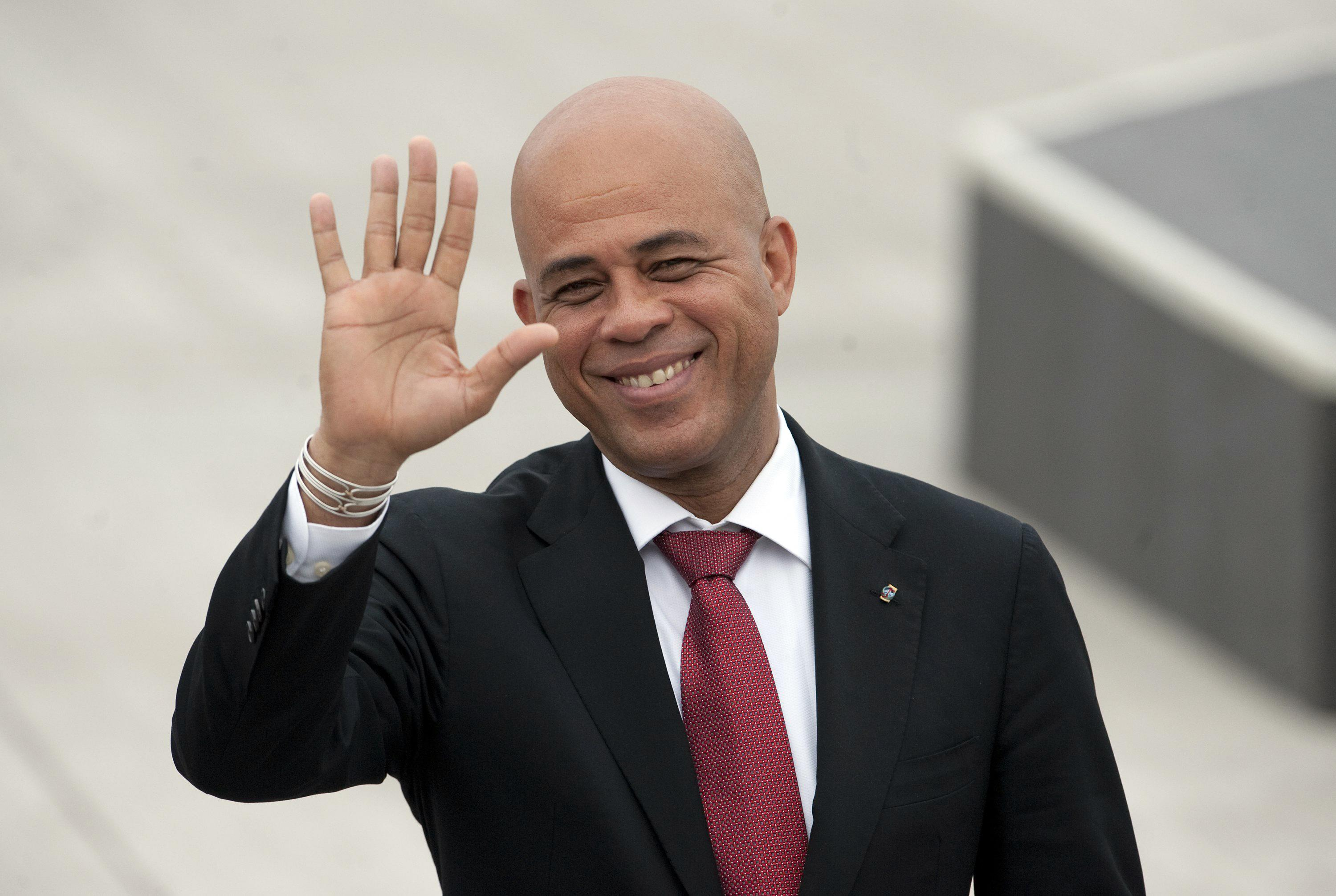 The President of Haiti Michel Joseph Martelly waves upon arrival at the international airport in Santiago on January 25, 2013 (AFP Photo/Claudio Santana)