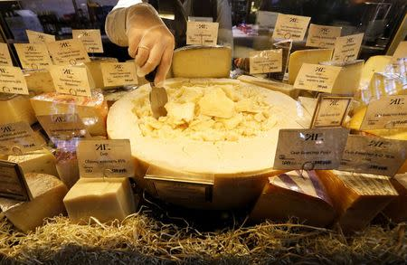 A worker arranges cheese for sale at a grocery store in St. Petersburg