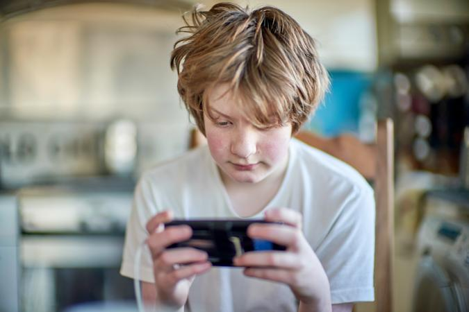 With his mobile phone in the kitchen